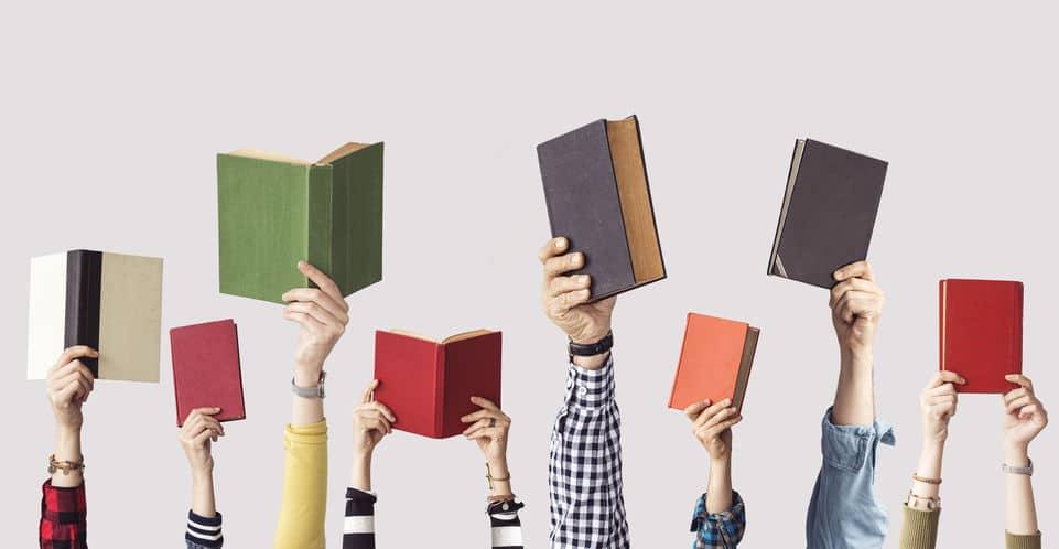 Mãos segurando livros.