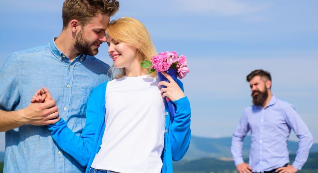 Casal de homem e mulher de mãos dadas e felizes. Ela segura em uma das mãos um buque de rosas na cor rosa. Ao fundo um outro homem observa o casal. Ele está com ciúmes de ver os dois juntos.