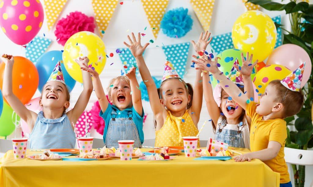 Festa de aniversário de crianças. São várias crianças festejando. Elas estão sorrindo e bem alegres. Todas usam chapéu de aniversário. Ao fundo uma parede branca decorada com bandeirolas e bexigas coloridas.