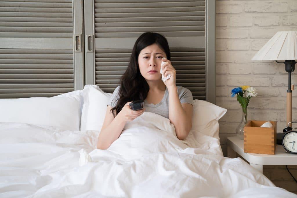 Mulher asiática deitada sobre a sua cama. Ela está com as costas encostada na janela, Ela acordou chorando porque sonhou com o seu ex-noivo,