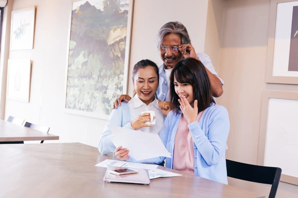 Família asiática reunida em uma linda sala branca e decorada com muitos quadros. Duas mulheres estão sentadas e um homem em pé. Eles estão lendo uma carta psicografada.