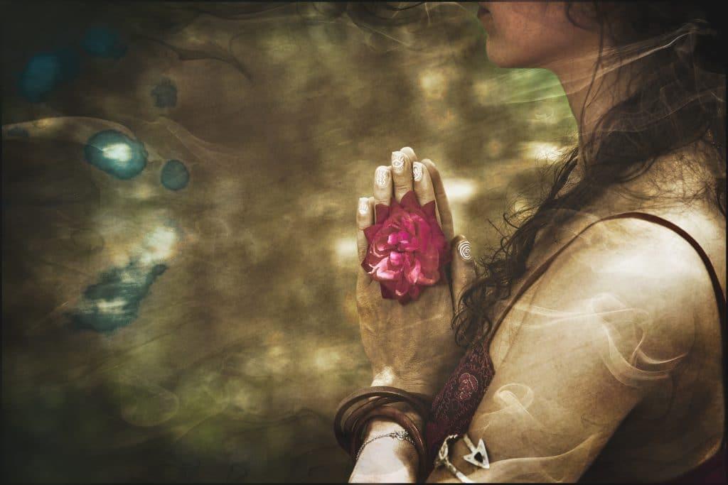 Imagem vintage na cor dourada de uma mulher de cabelos longos em posição de meditação. Nas mãos ela segura uma rosa.