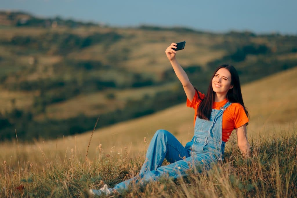 Uma mulher de cabelos longos, vestida de macacão jeans claro e camiseta laranja. Ela está tirando uma selfie em meio a natureza.