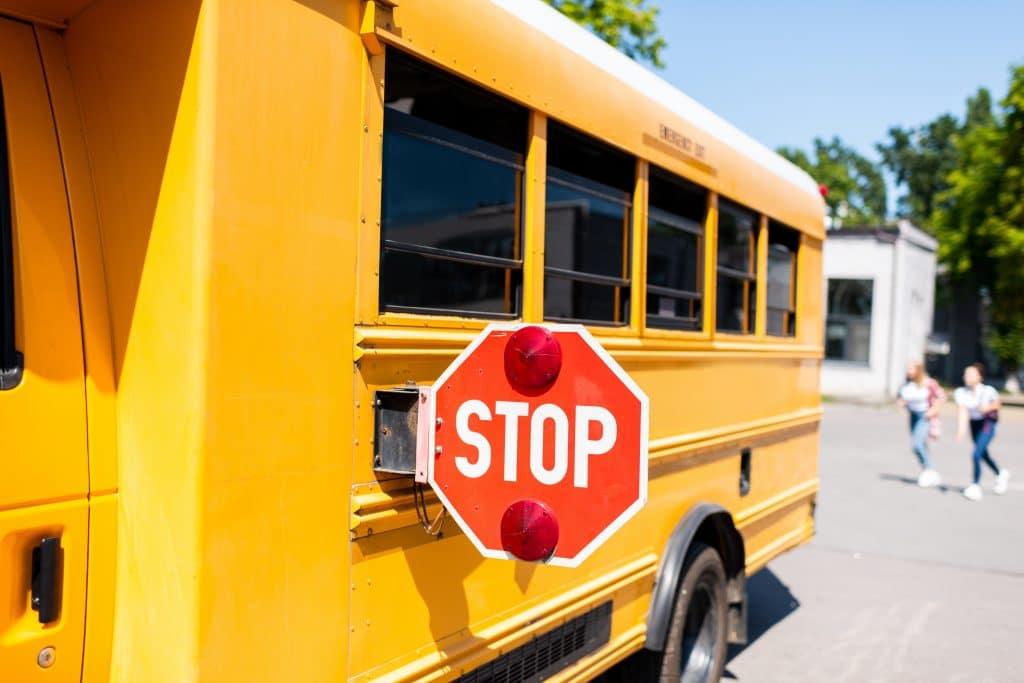 Ônibus amarelo escolar. Ele está parando esperando duas mulheres que estão correndo para apanhá-lo.