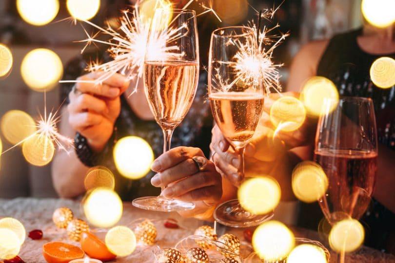 Duas pessoas brindando taça de champanhe.