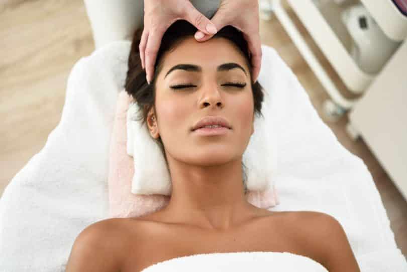 Mulher deitada recebendo massagem na testa.