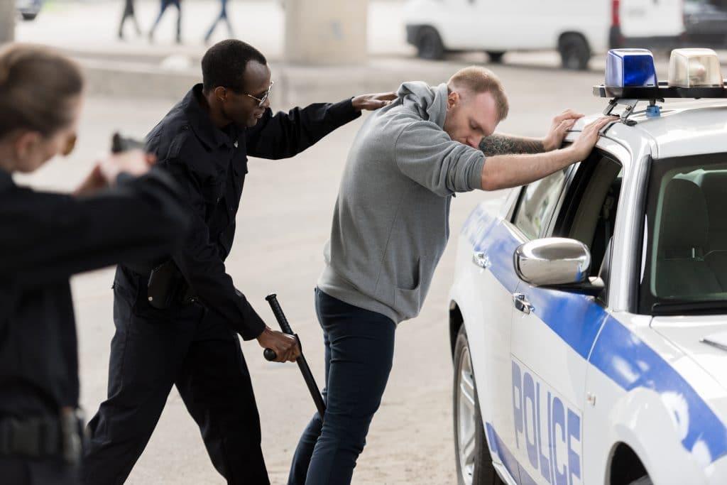 Policial homem e negro revistando e abordando um homem branco. Ele está com as mãos sobre o carro da polícia. Ao lado, uma policial mulher aponta uma arma para o suspeito.