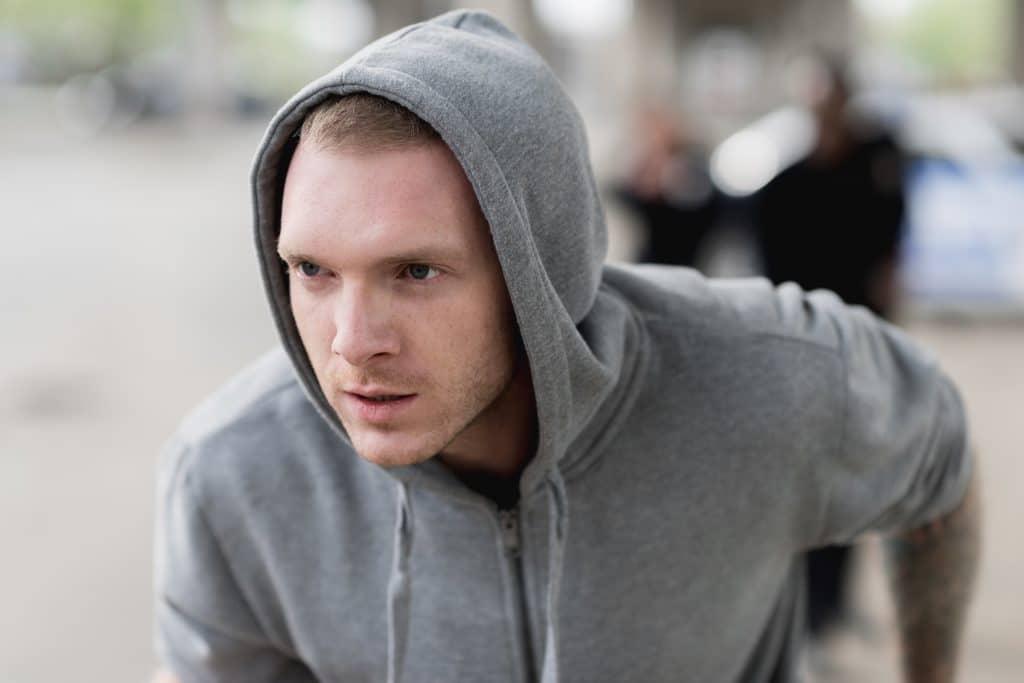 Jovem ladrão masculino, usando um moletom cinza com capuz e fugindo da polícia que está armada.