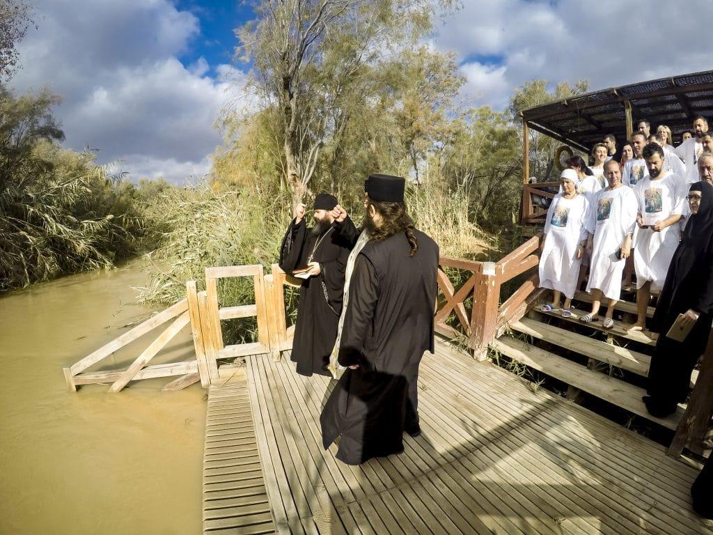 Ritual de batismo de pessoas adultas. Os celebrantes vestem túnicas pretas e os batizados túnicas brancas. A cerimônia acontece em um grande rio.