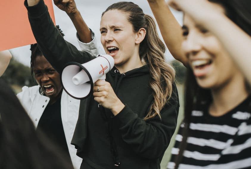 Grupo de mulheres protestando. Uma delas segura um cartaz, e outra fala em um megafone.
