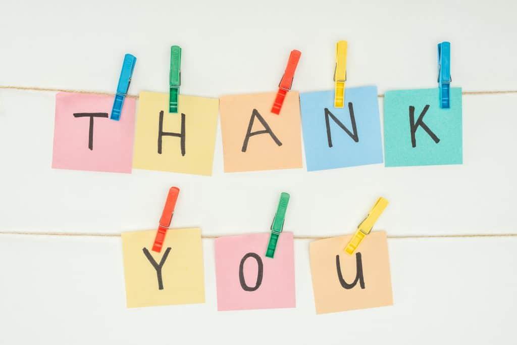 Palavra Thank You escrita em post-it coloridos e pendurados em um varal com pregadores coloridos.