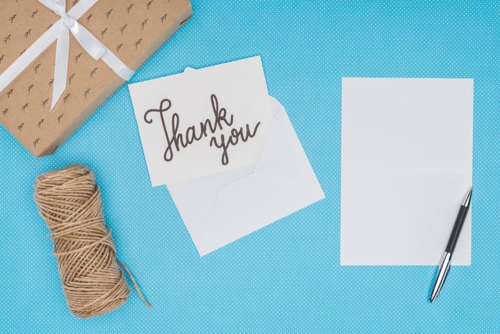 Palavra Thank You escrita em um papel branco. Ao lado um bloco de papel branco e sobre ele uma caneta prateada, um rolo de barbante e uma caixa de papelão fechada com um laço de fita branca.