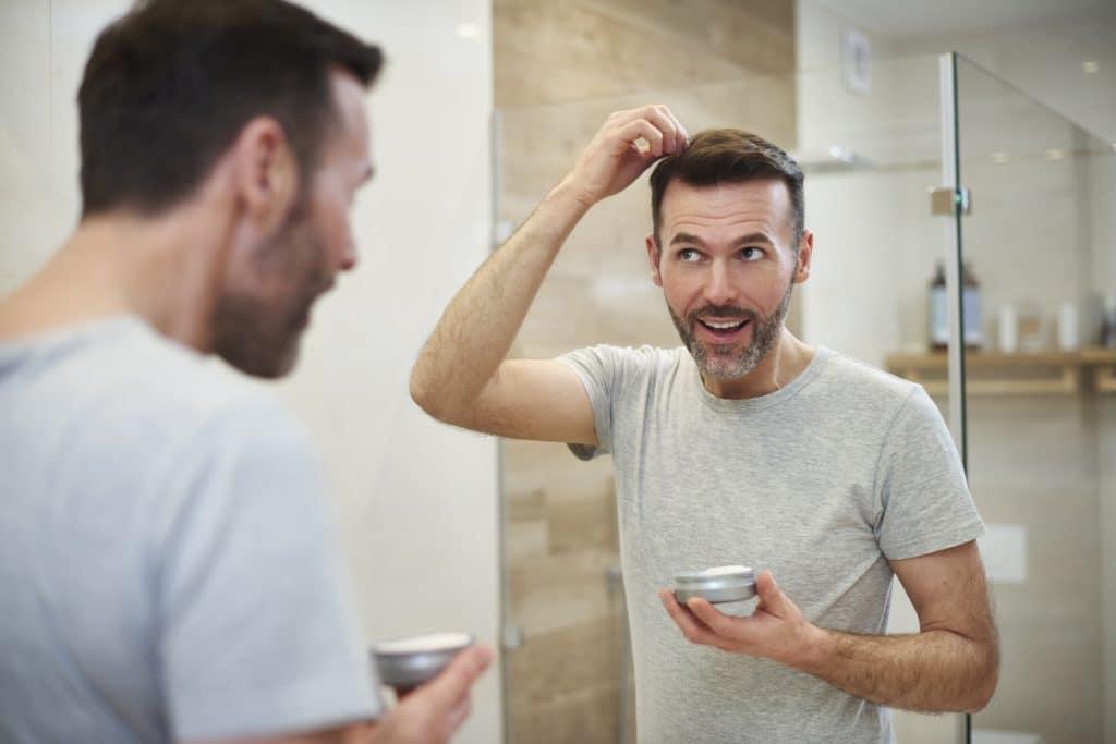 Imagem de um homem refletida no espelho de um banheiro. Ele está cuidado de sua pele e de seu cabelo.