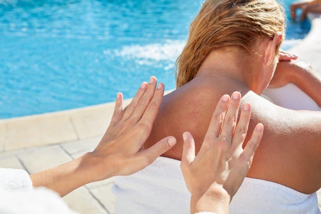 Mulher próxima a uma piscina. Ela está sentada e enrolada em uma toalha branca recebendo massagem na região das costas e nuca.