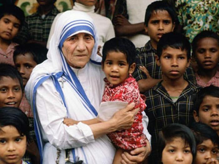 Madre Teresa de Calcutá segurando um menino em seu colo, rodeada por diversos outros meninos.