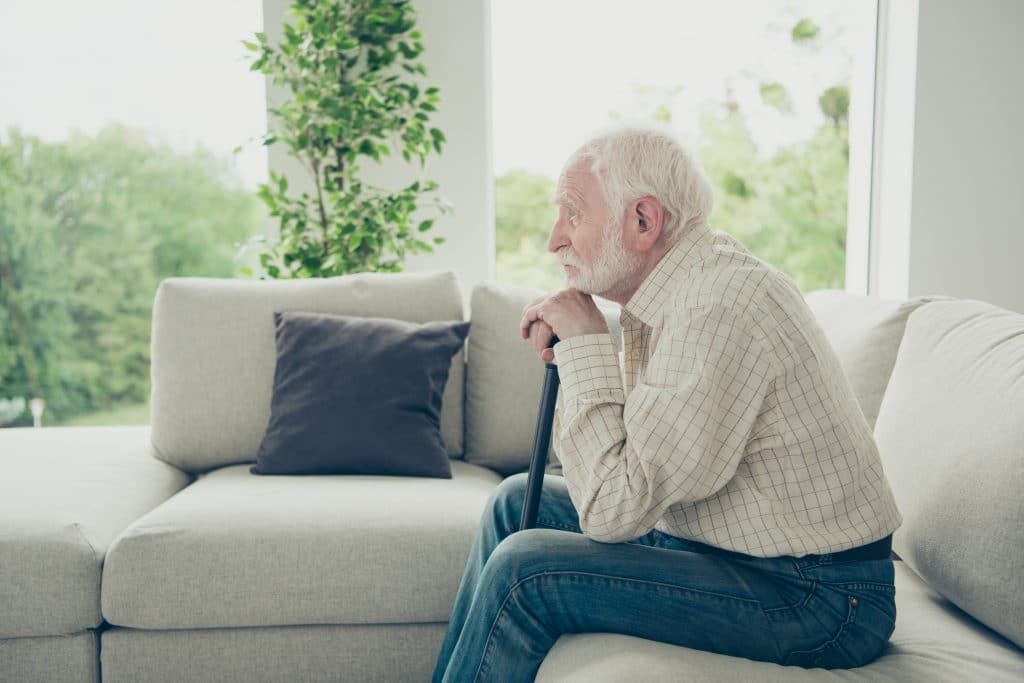 Idoso em sua sala sentando em seu sofá branco. Ele segura uma bengala e está pensando sobre a vida. Ele veste uma camisa xadrez bege e uma calça jeans azul clara.