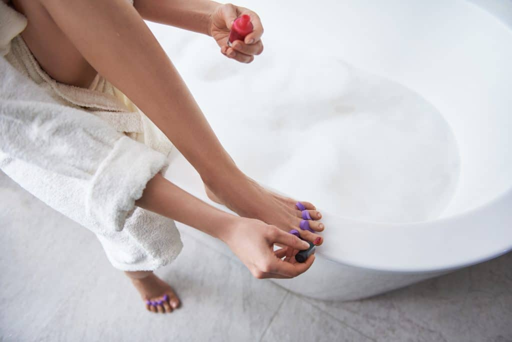 Mulher de roupão de banho branco, dentro do banheiro pintando as unhas dos pés com um deles sobre a sua banheira de tomar banho.