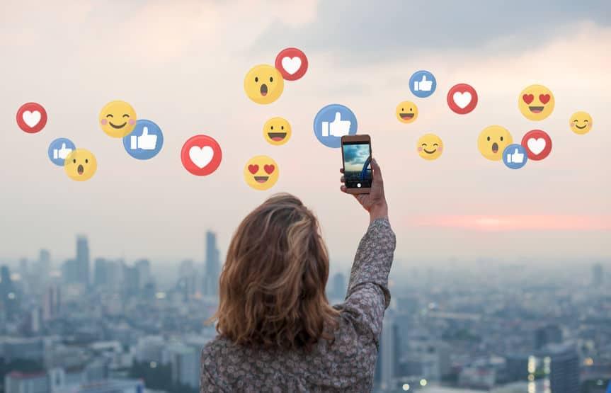 Mulher tirando foto do pôr do sol com seu celular, e vários ícones de reações de redes sociais como curtiu, amei, entre outros, estão ao redor dela.