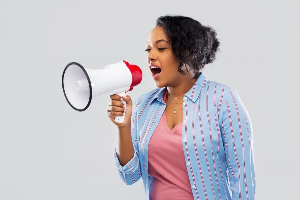 Mulher negra vestindo uma camisa azul clara com listras vermelhas segurando um megafone nas cores branco e vermelho. Ela está falando no megafone palavras de empoderamento feminino.