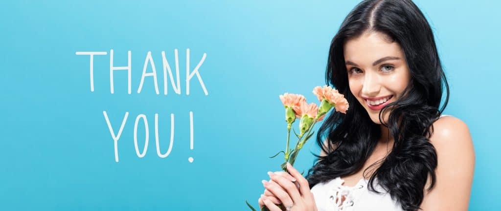 Mulher clara de cabelos longos pretos sehurando três ramos de cravo cor de rosa. Ao fundo, uma parede azul onde está escrito em branco a palavra THANK YOU!