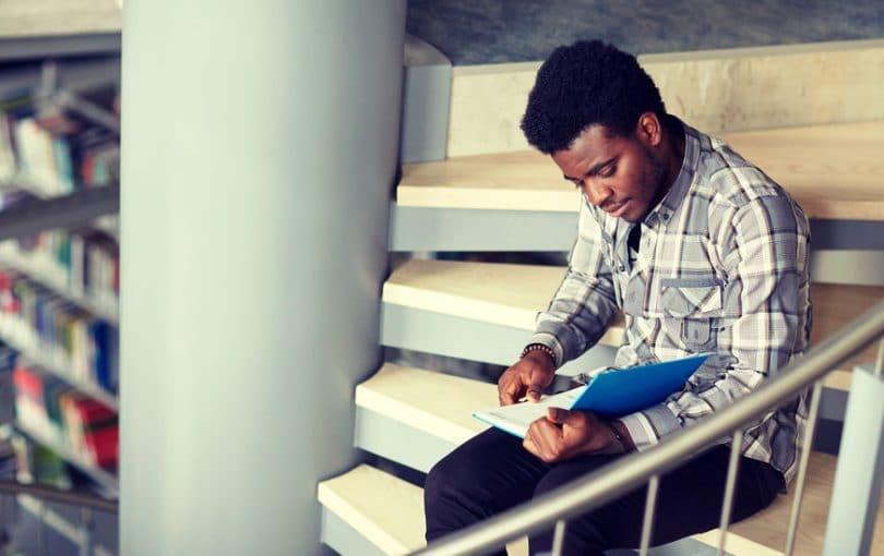 Homem lendo nas escadas.