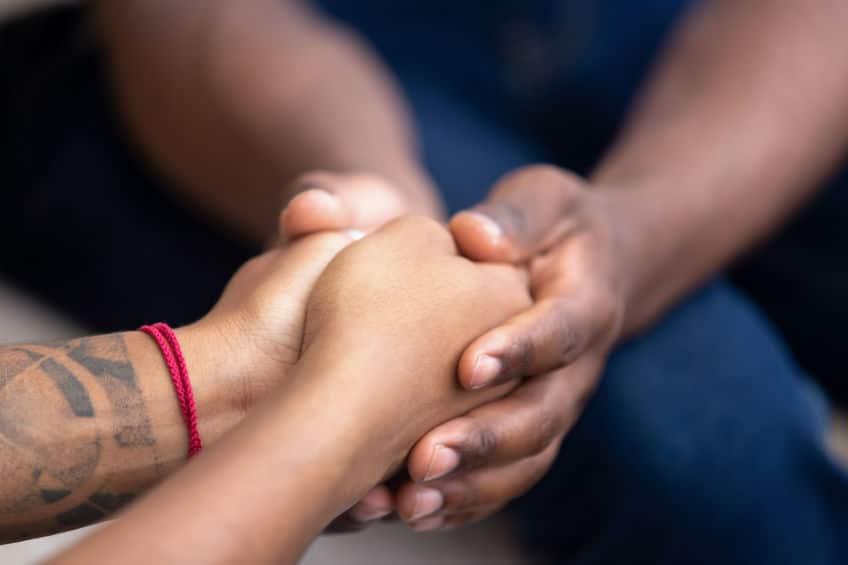 Imagem ampliada de uma pessoa sentada segurando as mãos de outra.