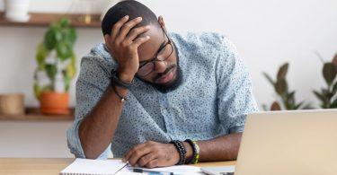 Homem exausto trabalhando em computador, apoia sua cabeça em seu braço direito.