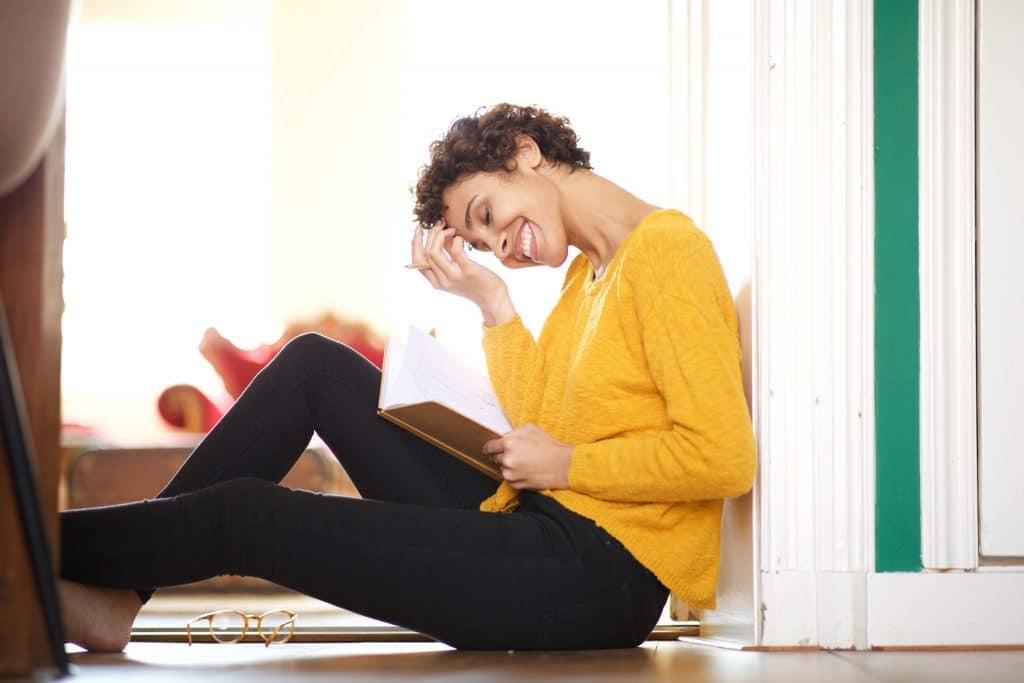 Moça sentada no chão com as costas encotada na parede. Ela veste uma blusa amarela e uma calça preta e está lendo uma carta com mensagem espírita.