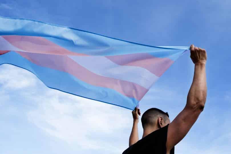 Homem branco segurando bandeira do orgulho transsexual.
