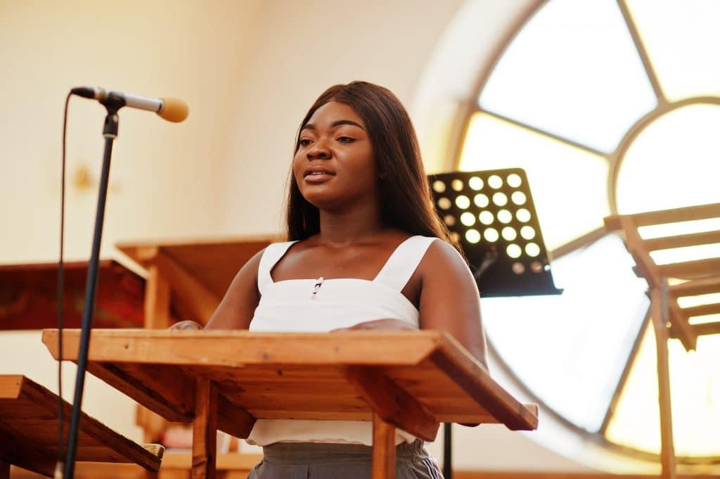 Mulher negra com um cabelo longo Ela veste uma blusinha a cor branca. Ela está dentro da igreja, na frente do púlpito e próxima ao microfone. Ela vai cantar.