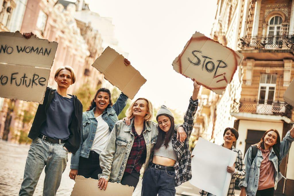 Grupo de mulheres ativistas em plena manifestação em prol do empoderamento feminino. Elas estão na rua e seguram cartazes com vários dizeres em torno do empoderamento feminino.