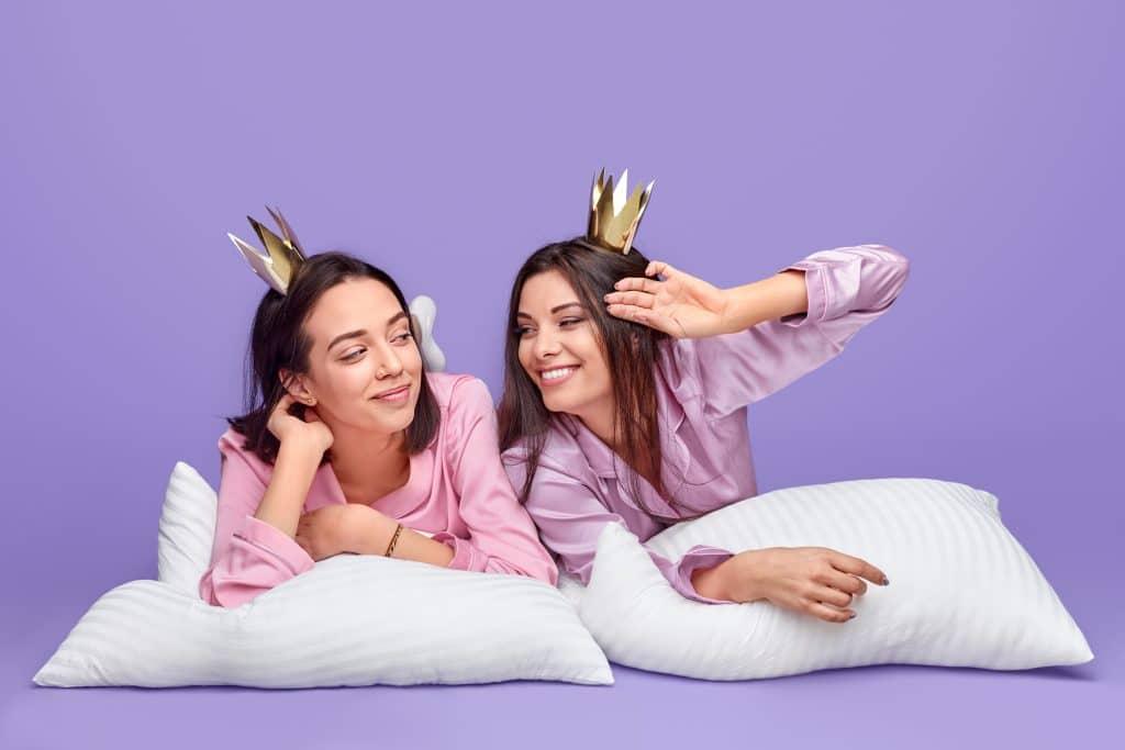 Duas mulheres de bruço em dois travesseiros brancos, sendo uma mulher em cada um. Elas vestem um pijama rosa e usam coroas douradas.
