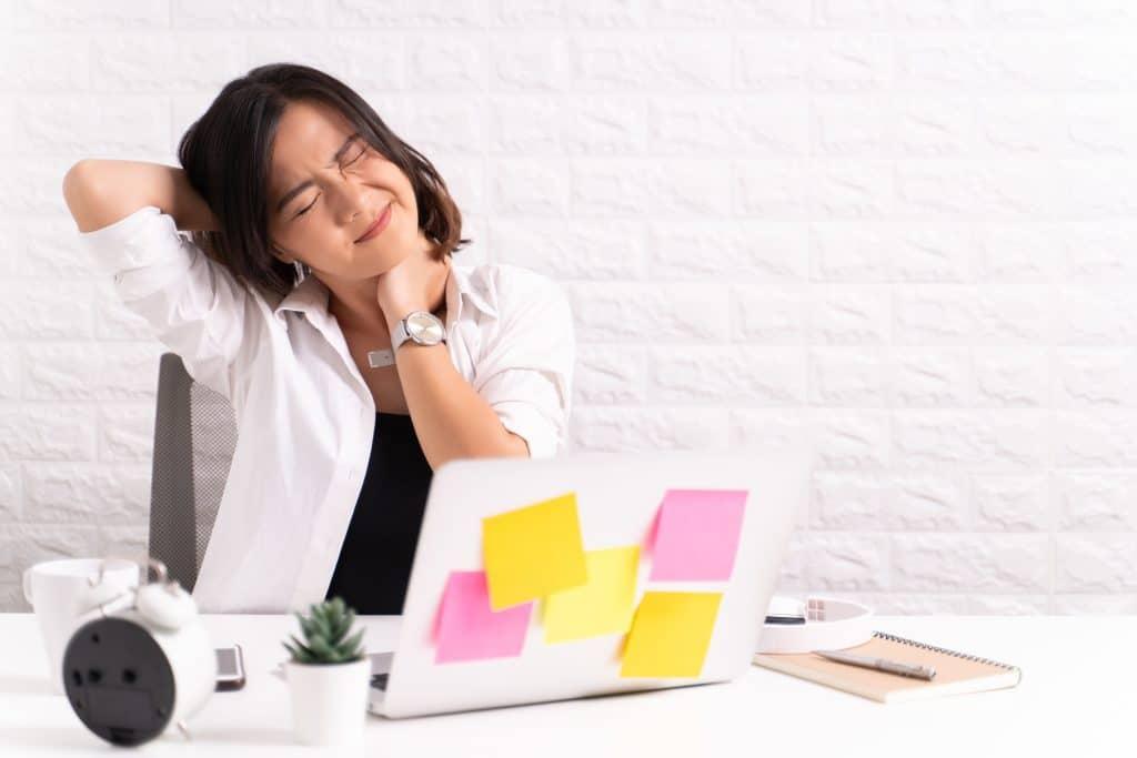 Mulher em sua sala de escritório com paredes e decoração branca. Ela está de frente para o notebook cheio de post-it colorido. Ela está com dores na nuca, pois suas mãos estão sobre ela.