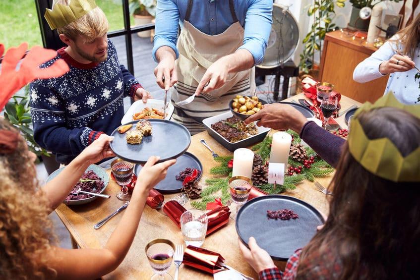 Grupo de pessoas ao redor de uma mesa se servindo com comida vegetariana.