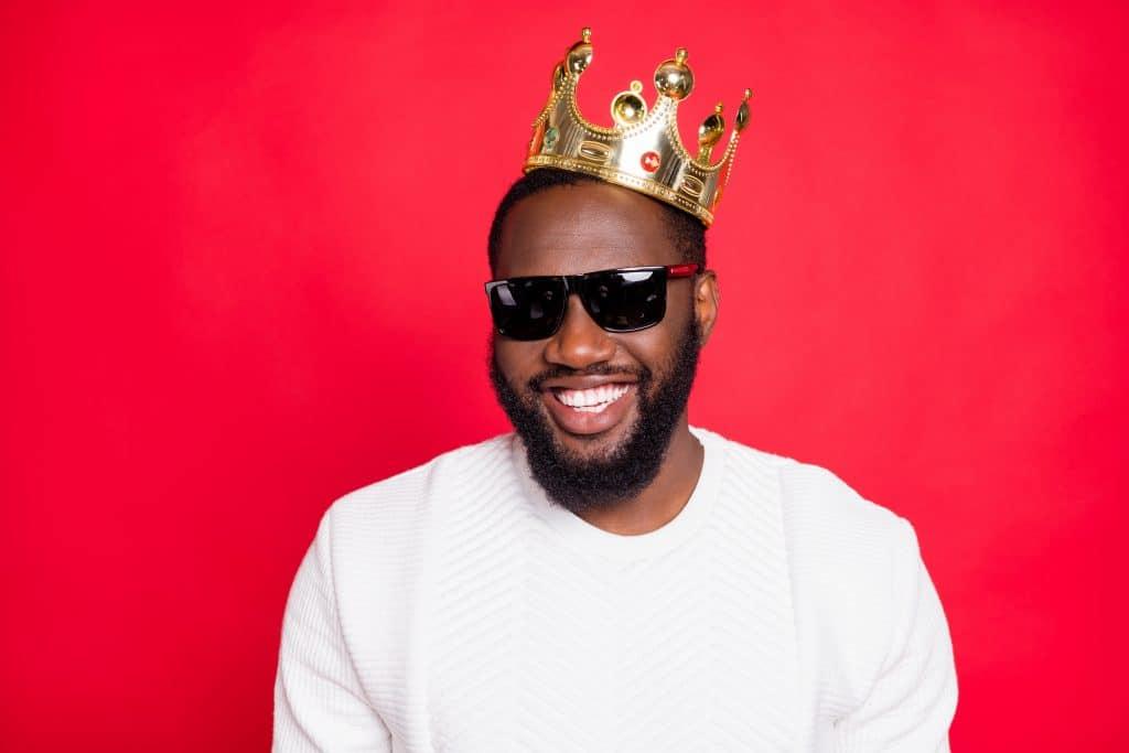 Homem negro com barba e bigode. Ele está usando um óculos preto e uma coroa dourada. Ele está sorrindo e bem feliz.