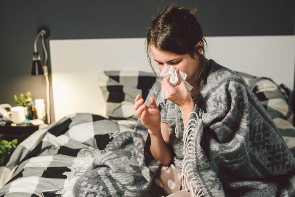 Mulher em seu quarto sentada em sua cama de casal. Ela está com uma coberta sobre as suas costas e soando o seu nariz.