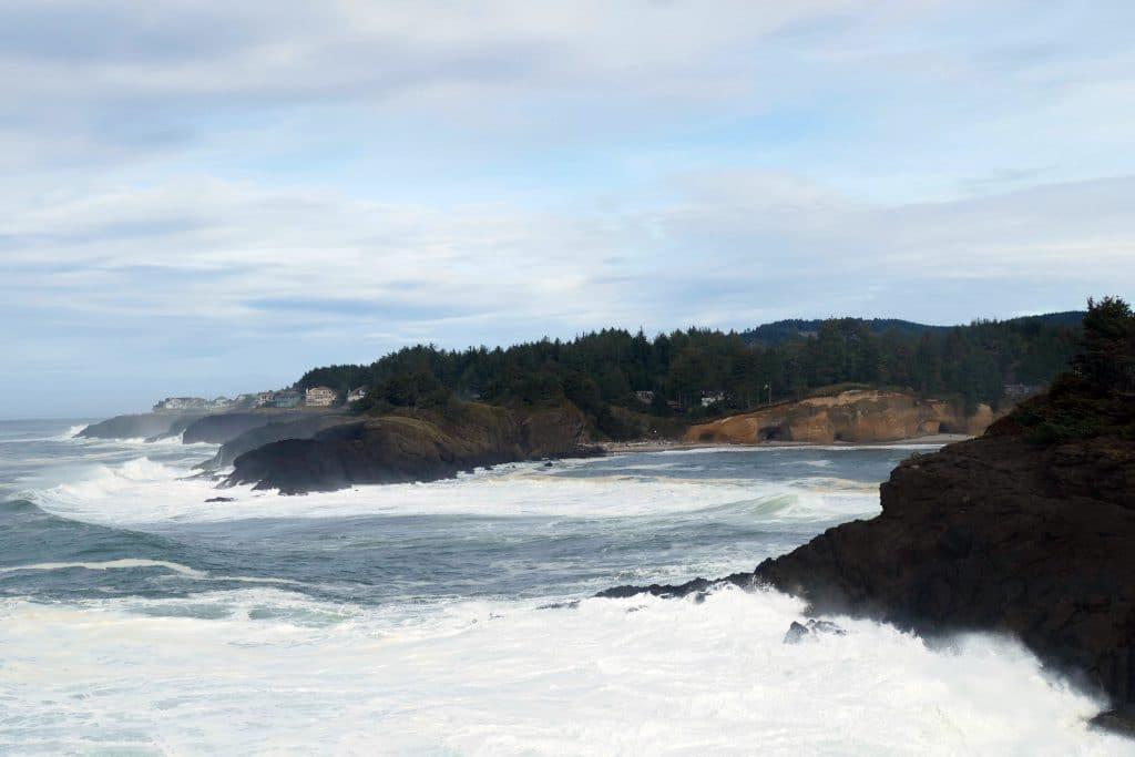 Mar agitado com ondas que quebram nas rochas da encosta da praia. O céu está meio encoberto e com algumas nuvens.