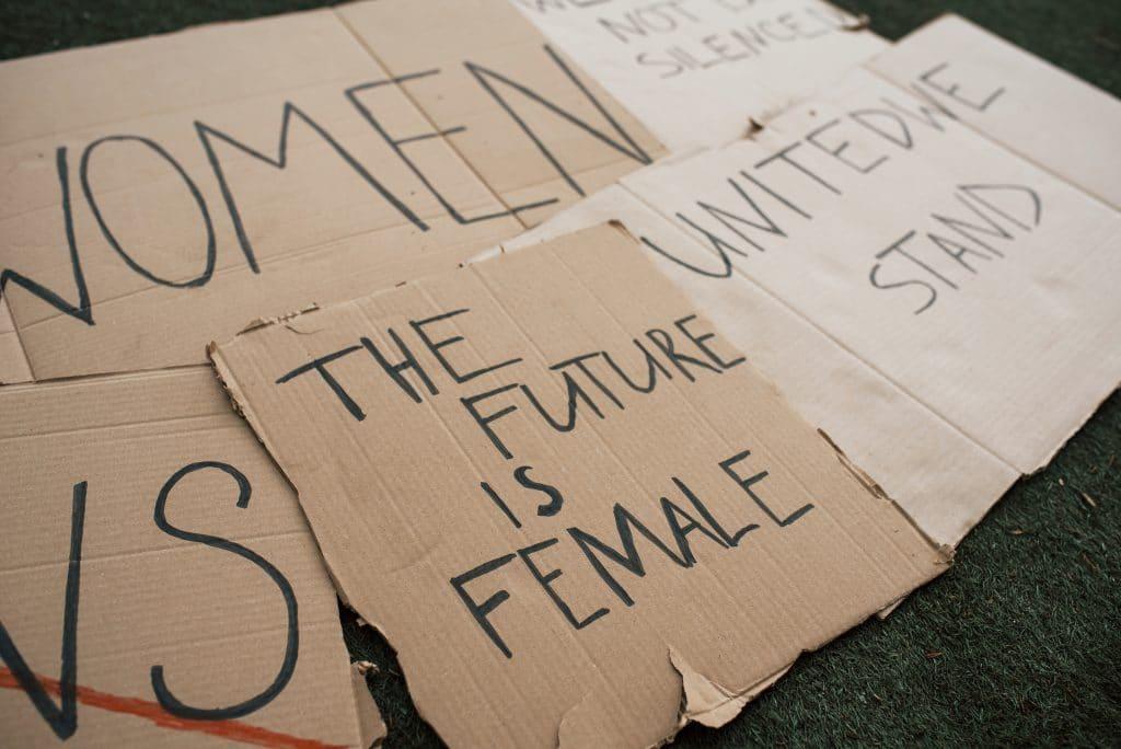Vários cartazes com diferentes citações feministas escritas à mão com canetão preto. Todos os cartazes estão espalhados pelo chão.