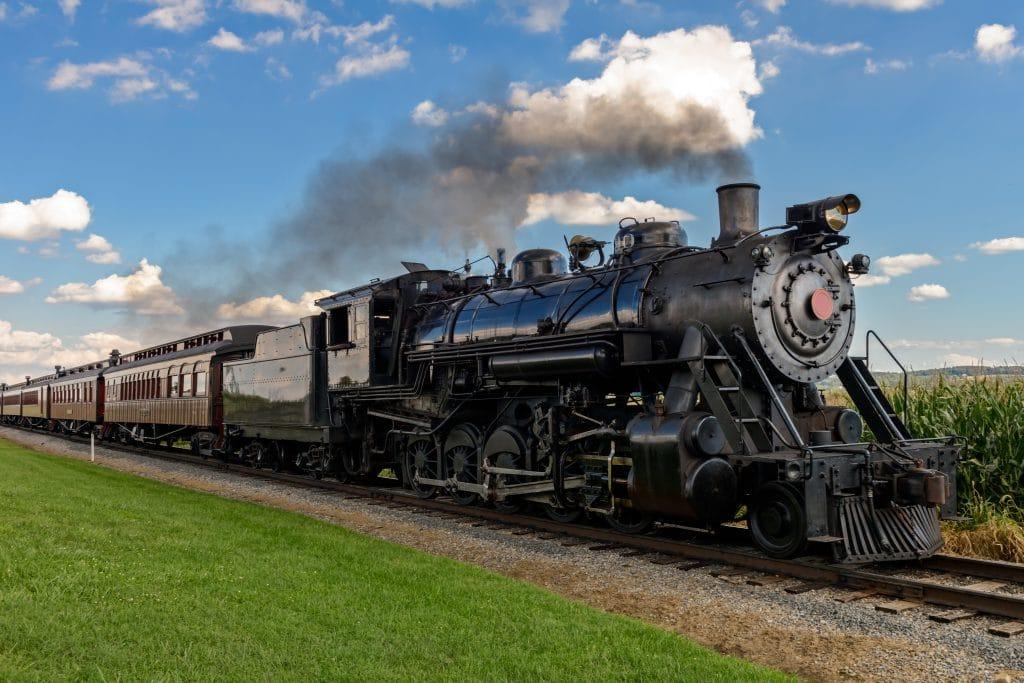 Trem sobre os trilhos. Ele é antigo, sua cor é preta. Está soltando fumaça e ao lado do trilho gramado e plantação.