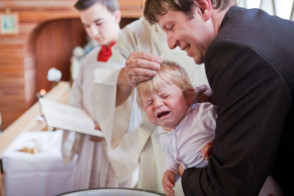 Criança sendo segurando pelo padrinho ao ser batizada.