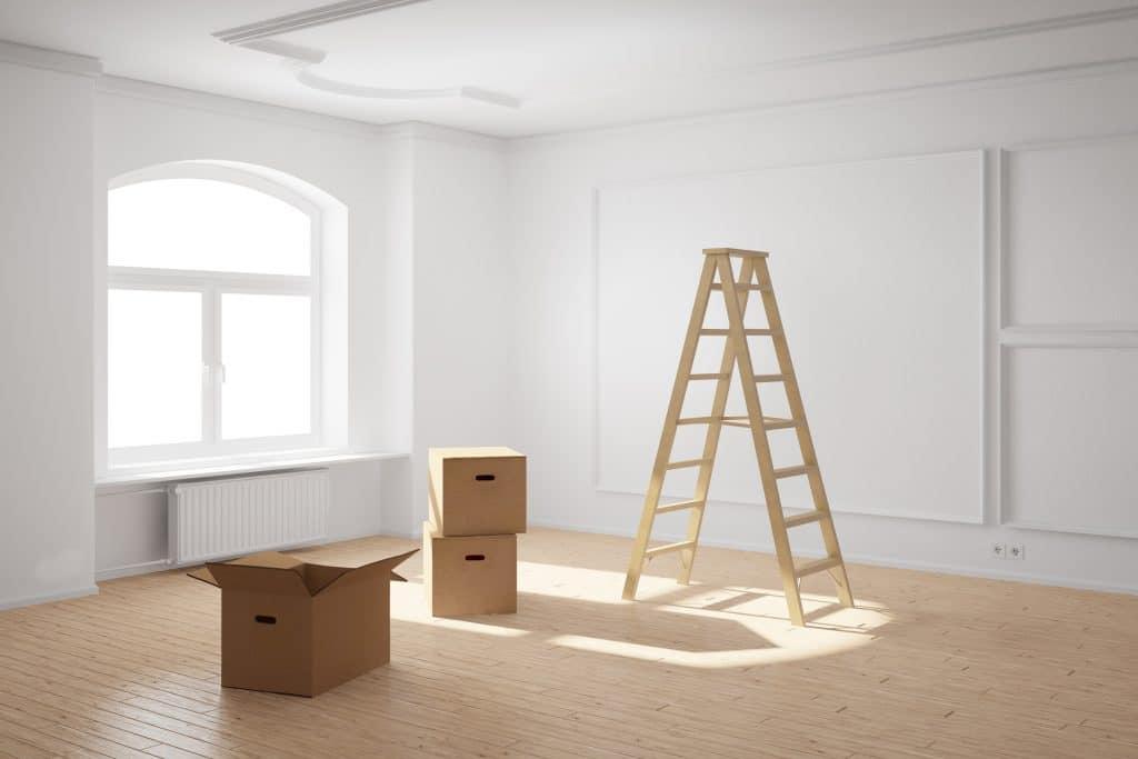 Escada de madeira dentro de uma sala ampla e na cor branca. Ao lado da escada três caixas de papelão. Uma delas está aberta e as outras estão fechadas.