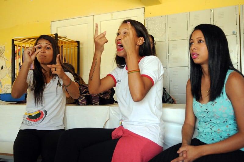 Três meninas se comunicam com libras com algúem atrás da câmera