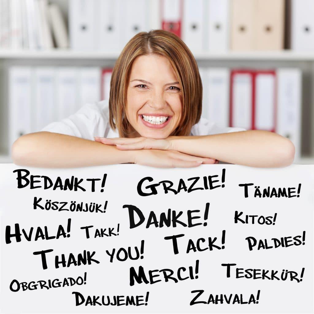 Palavra gratidão escrita em diversos idiomas. Atrás das palavras um mulher feliz e sorridente, sendo grata por tudo que aconteceu em sua vida.