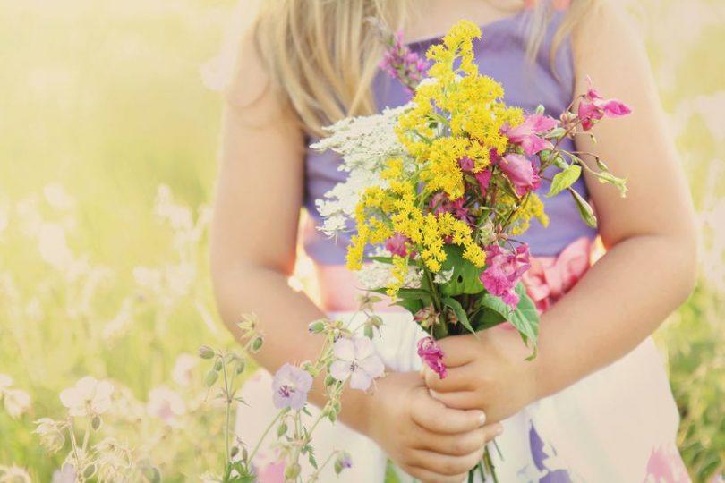 Menina usando vestido segurando um buque de flores em uma campina. A foto corta sua cabeça, vemos apenas seu corpo.