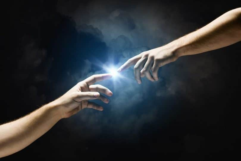 """Dois dedos se tocando e uma luz emergindo entre eles. Uma releitura da obra """"A Criação de Adão"""" de Michelangelo."""
