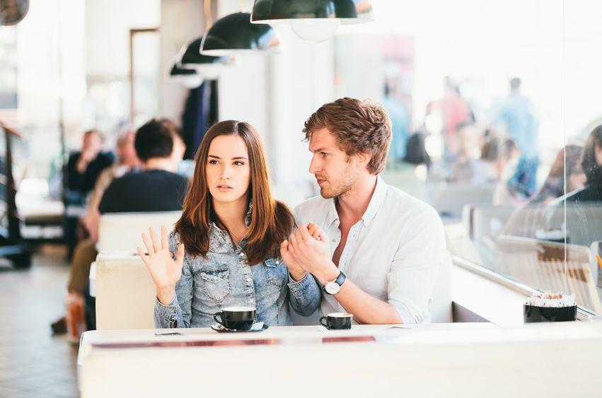 Casal sentado lado a lado numa lanchonete. O homem olha para a mulher e segura sua mão esquerda. A mulher olha para o outro lado, e a mão direita levantada.
