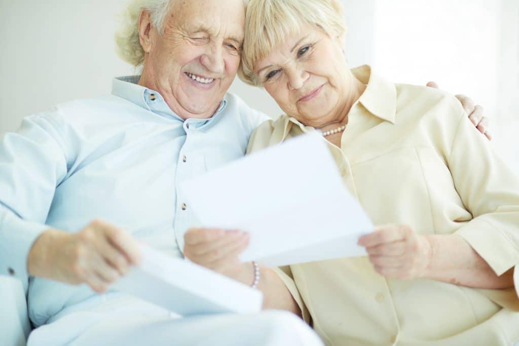 Casal de homem e mulher idosos. Ele veste uma roupa branca e ela um blusa creme e um colar de pérolas. Ambos estão sentados em um sofá lendo uma carta psicografada.