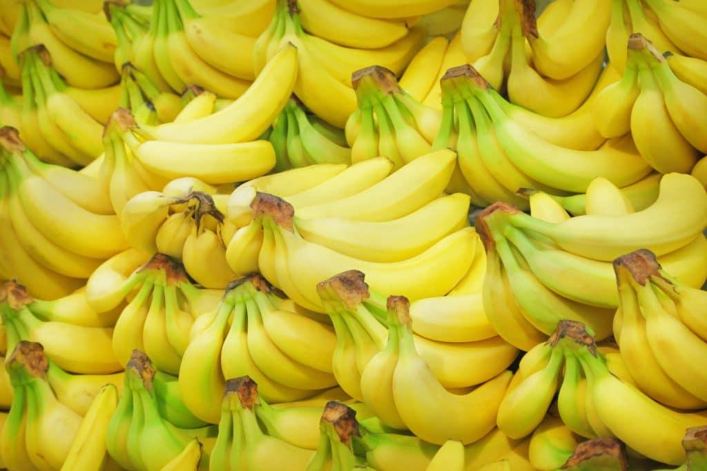 Pilhas de cachos de bananas amarelinhas disponíveis em uma bancada de supermercado.