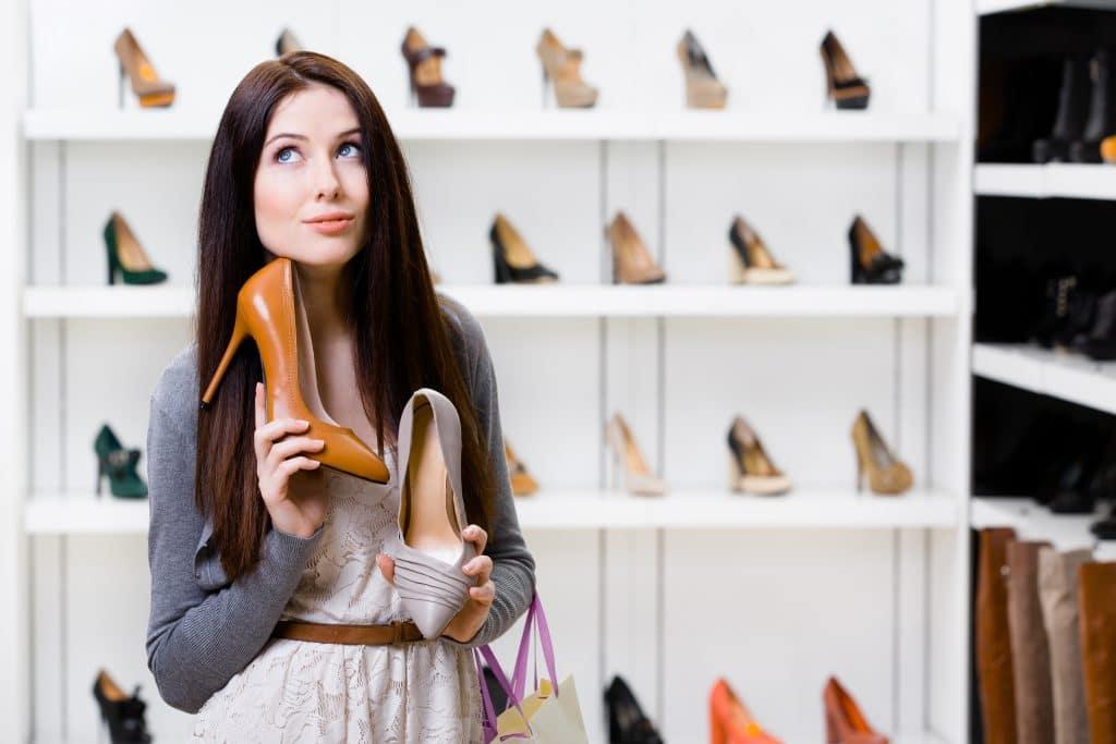 Mulher morena de cabelos longos. Ela está vestindo um vestido branco e um suéter cinza. Ela segura em suas mãos dois sapatos: um na cor marrom e outro na cor cinza. Ao fundo quatro prateleiras brancas cheias de sapatos femininos de salto alto com várias cores.