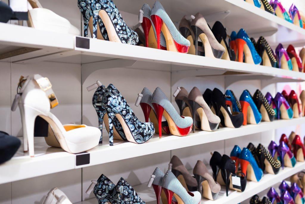 Cinco prateleiras brancas cheias de sapatos femininos de salto alto. Todos são coloridos.